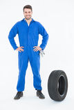 Smiling mechanic with hands on hips standing by tire Royalty Free Stock Photos