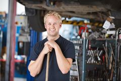 Smiling mechanic holding broom Royalty Free Stock Photo