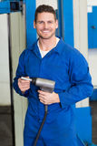 Smiling mechanic holding power drill. At the repair garage Royalty Free Stock Image