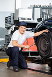 Smiling Mechanic Holding Rim Wrench By Car Royalty Free Stock Photos