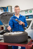 Smiling mechanic inflating the tire Royalty Free Stock Photo