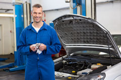Smiling mechanic looking at camera. At the repair garage Royalty Free Stock Photography