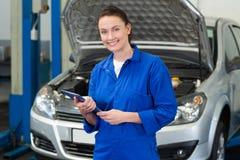 Smiling mechanic looking at camera. At the repair garage Royalty Free Stock Images
