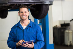 Smiling mechanic looking at camera using tablet Stock Photo