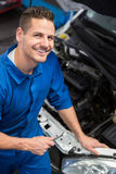 Smiling mechanic looking up at camera Royalty Free Stock Photos