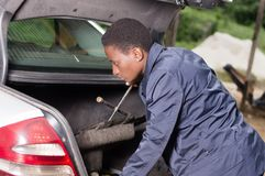 Young smiling mechanic looking in the trunk of a car in the garage. A smiling mechanic looks for her work tools in the back of a car in the garage Stock Photo