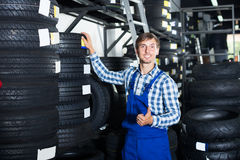 Smiling mechanic man working with car tires in workshop Royalty Free Stock Images