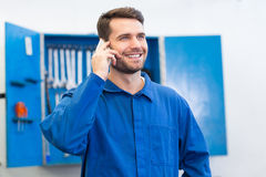 Smiling mechanic on the phone. At the repair garage Stock Image