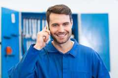 Smiling mechanic on the phone. At the repair garage Royalty Free Stock Photography