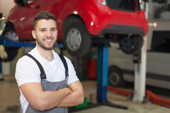 Smiling mechanic posing in auto repair shop Stock Photography