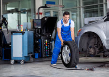Smiling mechanic pushes the tire. In a workshop Stock Photography