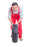 Smiling mechanic pushing car wheel with tire Royalty Free Stock Photography