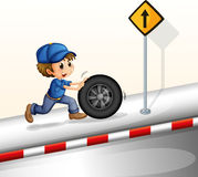 A smiling mechanic pushing the tire Royalty Free Stock Photography