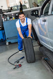 Smiling mechanic repair and  pushing a black tyre Stock Image