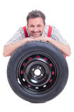 Smiling mechanic resting head on tire Stock Image