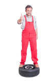 Smiling mechanic showing like standing on a car wheel Royalty Free Stock Photo