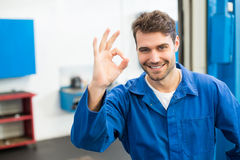 Smiling mechanic showing ok sign. At the repair garage royalty free stock image