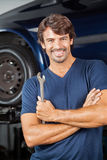 Smiling Mechanic Standing Arms Crossed. Portrait of smiling mechanic holding wrench while standing arms crossed at repair shop royalty free stock image