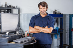 Smiling Mechanic Standing Arms Crossed In Repair. Portrait of smiling male mechanic standing arms crossed by computer in auto repair shop Stock Photos