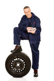 Smiling mechanic with a tire and tablet Royalty Free Stock Photography