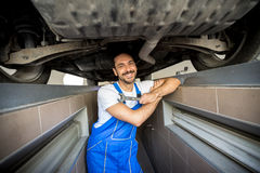 Smiling mechanic. Underneath a car Stock Photo