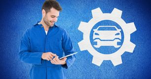 Smiling mechanic using digital tablet against blue background Royalty Free Stock Photography
