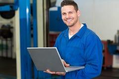 Smiling mechanic using his laptop. At the repair garage Stock Image