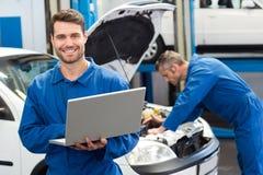 Smiling mechanic using a laptop. At the repair garage Royalty Free Stock Image