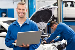 Smiling mechanic using a laptop. At the repair garage Stock Images