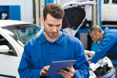 Smiling mechanic using a tablet pc. At the repair garage Royalty Free Stock Photo