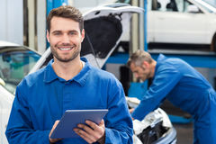 Smiling mechanic using a tablet pc. At the repair garage Stock Photo