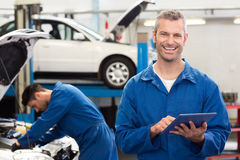 Smiling mechanic using a tablet pc. At the repair garage Stock Image