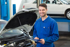 Smiling mechanic using a tablet pc. At the repair garage Royalty Free Stock Photography