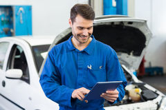 Smiling mechanic using tablet pc Royalty Free Stock Photography