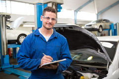 Smiling mechanic writing on clipboard. At the repair garage Royalty Free Stock Photography