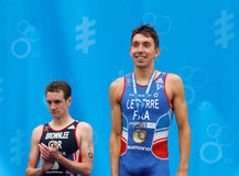 The smiling medalist triathletes Brownlee and Le Corre on the po Stock Photo