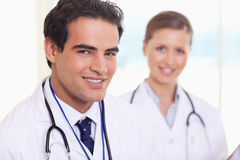 Smiling medical assistants standing. Smiling young medical assistants standing next to each other royalty free stock photography