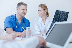 Smiling medical colleagues enjoying conversation at work stock images