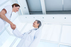 Smiling medical colleagues shaking hands Stock Photos