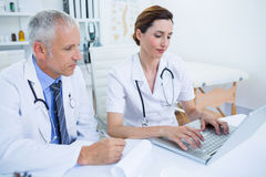 Smiling medical colleagues working with laptop Royalty Free Stock Images