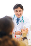 Smiling medical doctor giving pills to patient Stock Image