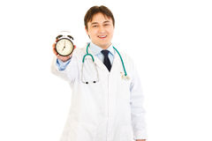 Smiling medical doctor holding alarm clock in hand Stock Photos