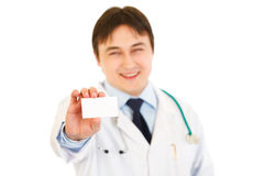Smiling medical doctor holding blank business card. In hand isolated on white Stock Photography