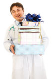 Smiling medical doctor holding gifts in hands Stock Photos
