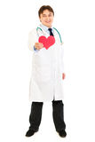 Smiling medical doctor holding paper heart in hand Stock Photo