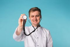 Smiling medical doctor man with stethoscope over blue background with copy space stock image