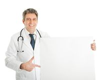 Smiling medical doctor presenting empty board. Smiling senior medical doctor presenting empty board. Isolated on white Royalty Free Stock Photo