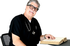 Smiling medical doctor reading a book Royalty Free Stock Photography