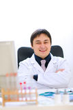 Smiling medical doctor sitting in cabinet Royalty Free Stock Image