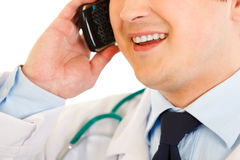 Smiling medical doctor talking on mobile. Close-up Royalty Free Stock Photo